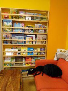Buntes Bücherregal mit Kinderbüchern und orangefarbenes Sofa