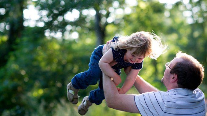 Vater wirft Tochter in die Luft beim Spielen